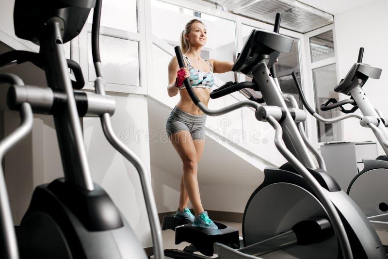 Mulher nova bonita da aptidão no gym que exercita nas máquinas do xtrainer Fazer modelo do ajuste atrativo cardio- gordo imagens de stock royalty free