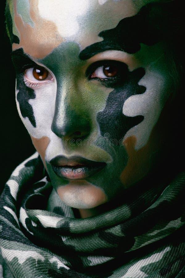 A mulher nova bonita da forma com roupa militar do estilo e a cara pintam a composição, cores caqui, celebração do Dia das Bruxas fotografia de stock