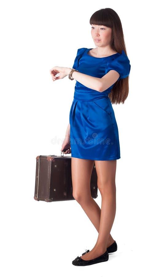 A mulher está sentando-se na mala de viagem de couro velha imagem de stock royalty free