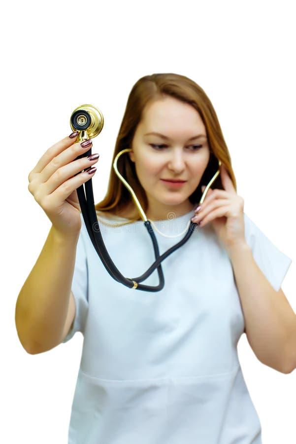 Mulher nova bonita do doutor que usa o estetoscópio isolado no fundo branco Um doutor fêmea com um estetoscópio que escuta para e fotos de stock