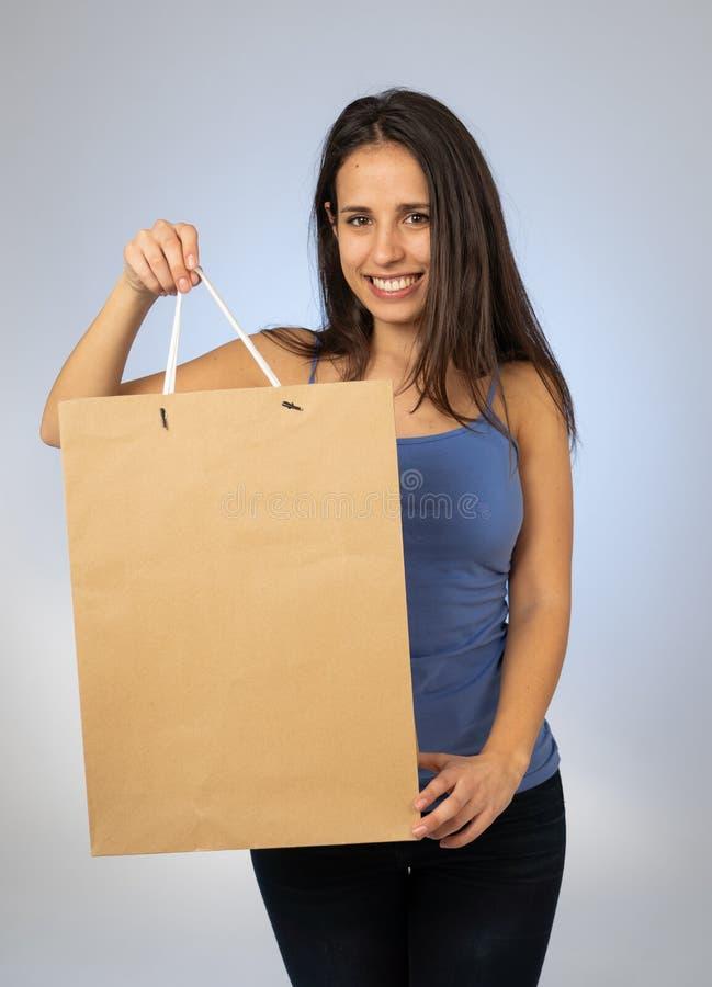 Mulher nova bonita do latino que guarda o saco de compras de papel com espaço da cópia imagem de stock