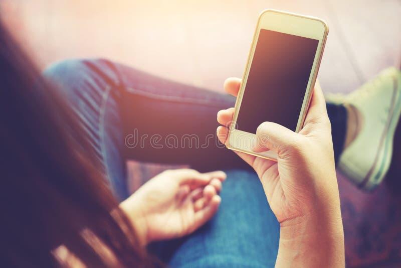 mulher nova bonita do moderno que usa o telefone esperto na cafetaria, imagem de stock