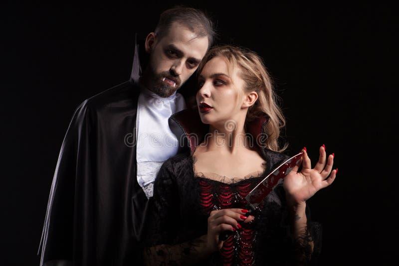 Mulher nova bonita do vampiro com uma lâmina coberta no sangue que olha seu homem vestido acima como Dracula para o Dia das Bruxa fotografia de stock