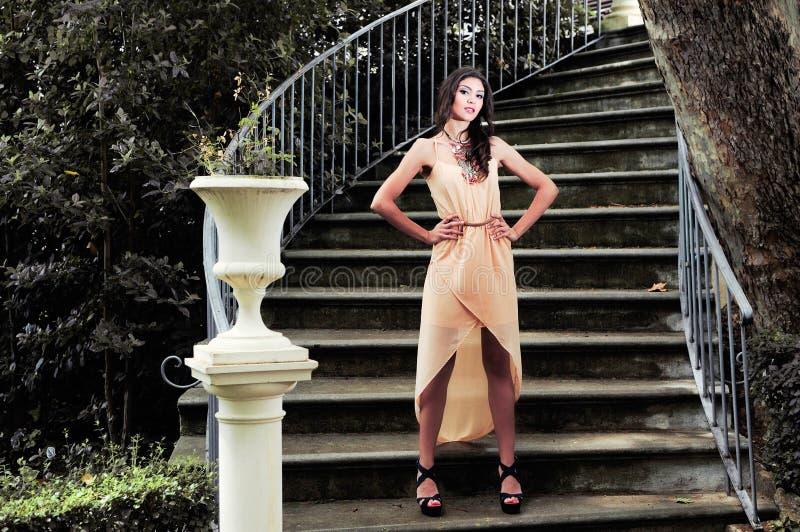 Mulher nova bonita em escadas de um jardim. foto de stock