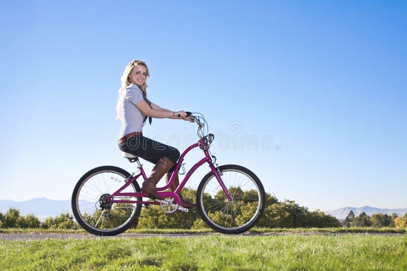 Mulher nova bonita em um passeio da bicicleta imagens de stock royalty free