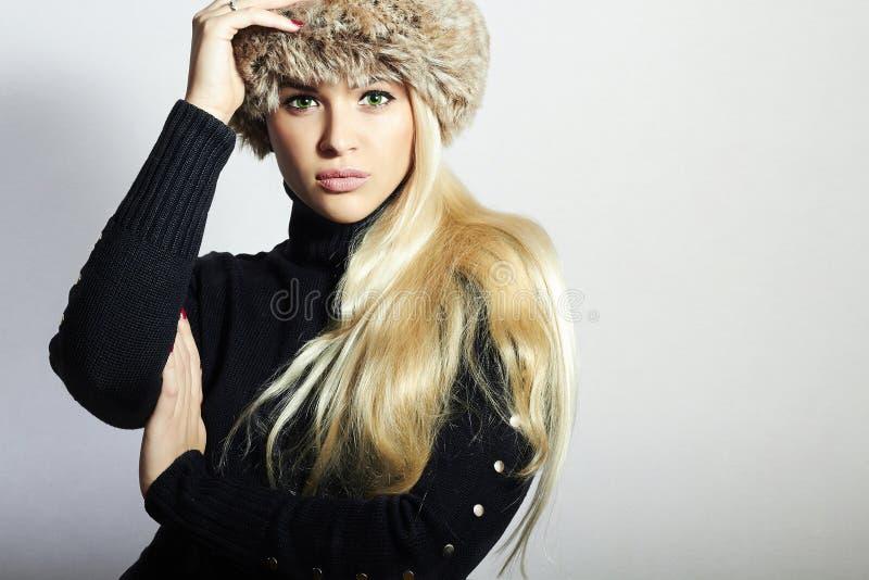 Mulher nova bonita no chapéu forrado a pele Menina consideravelmente loura Beleza da forma do inverno foto de stock royalty free
