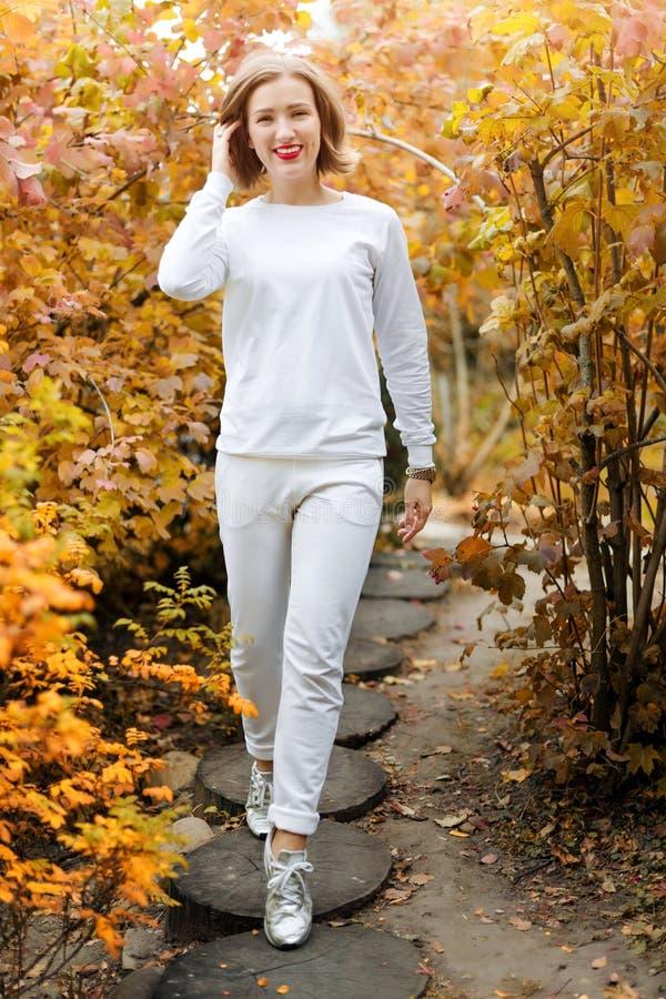 Mulher nova bonita no parque do outono Estação e conceito dos povos Modelo de forma louro que tem o divertimento no parque da que foto de stock royalty free