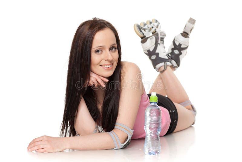 A mulher nova bonita nos rollerskates. imagem de stock