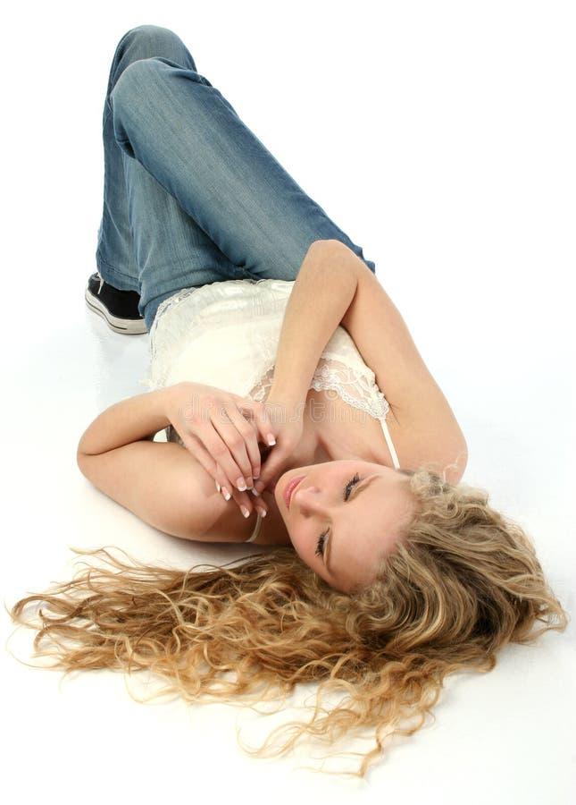 Mulher nova bonita que coloca no assoalho branco fotografia de stock royalty free
