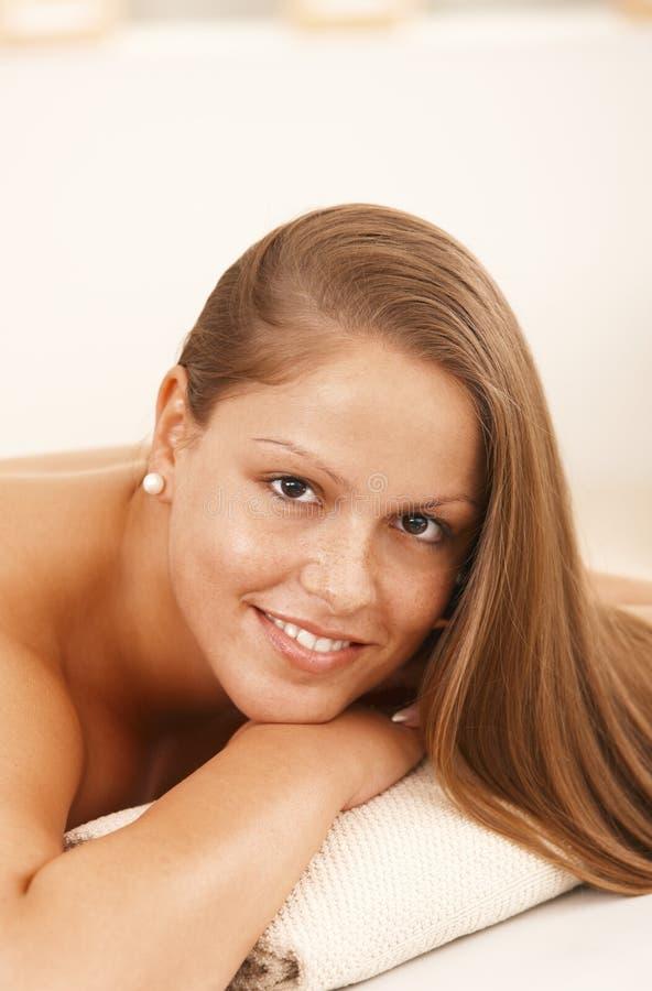 Mulher nova bonita que encontra-se na cama da massagem fotografia de stock royalty free
