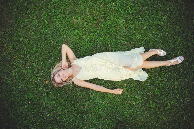 Mulher nova bonita que encontra-se na grama Conceito natural fresco do verão Vista de acima fotografia de stock royalty free