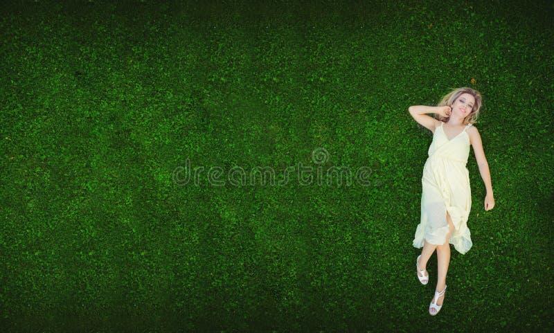 Mulher nova bonita que encontra-se na grama Conceito natural fresco do verão Vista de acima foto de stock royalty free