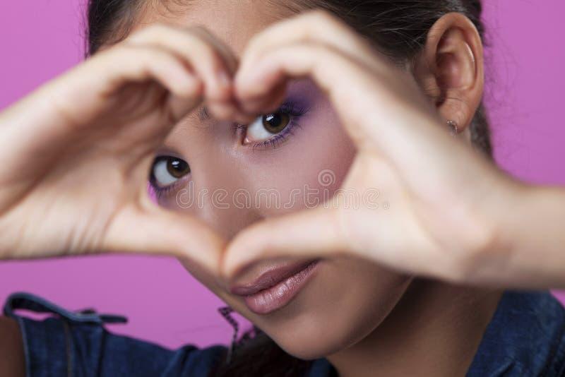 Mulher nova bonita que faz o coração com mãos fotos de stock