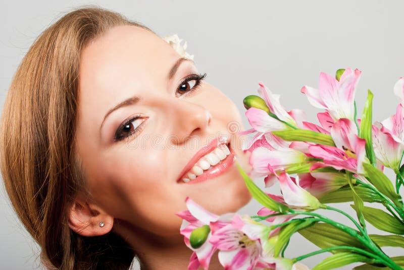 Mulher nova bonita que prende flores cor-de-rosa da mola fotos de stock royalty free