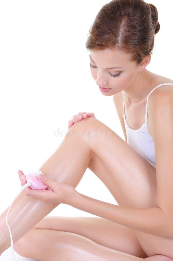 Mulher nova bonita que raspa seus pés fotos de stock