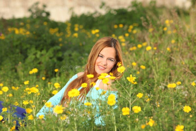 Mulher nova bonita que senta-se no prado fotografia de stock royalty free