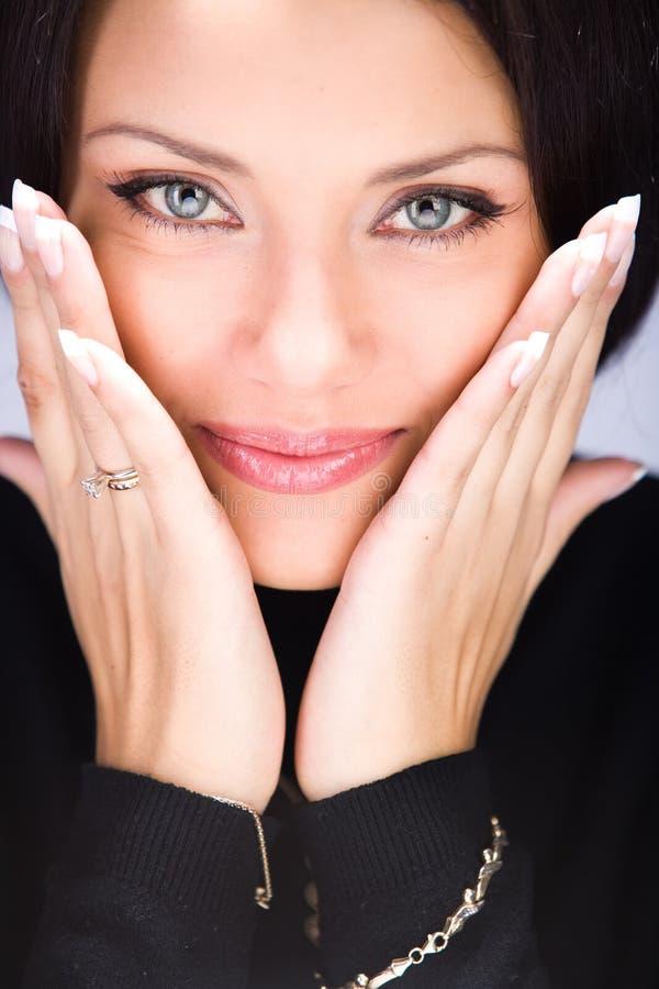 Mulher nova bonita que toca em sua face pelas mãos foto de stock