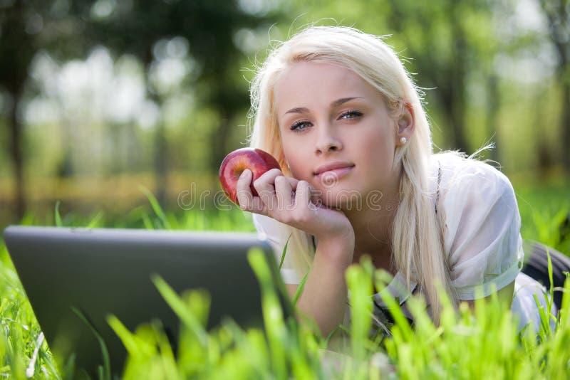Mulher nova bonita que usa o portátil no parque imagem de stock royalty free