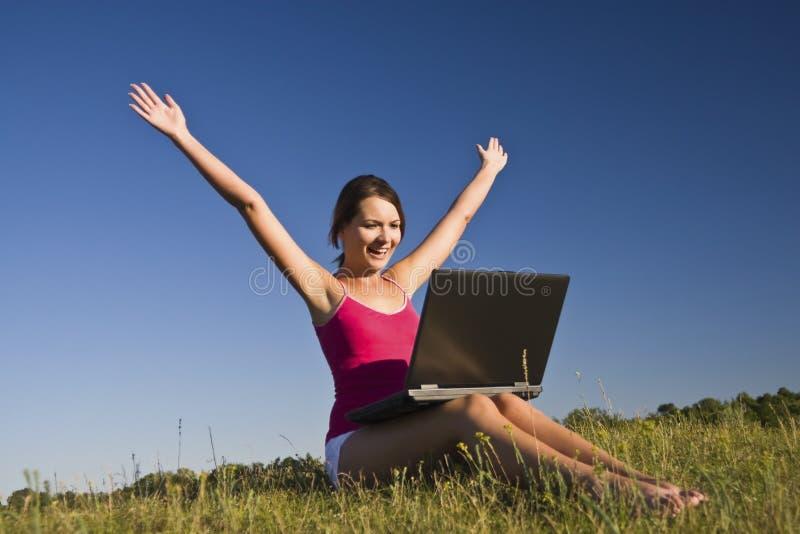 Mulher nova bonita que usa um portátil imagens de stock
