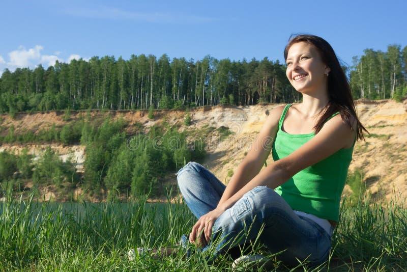 A mulher nova bonita senta-se em terra fotografia de stock royalty free