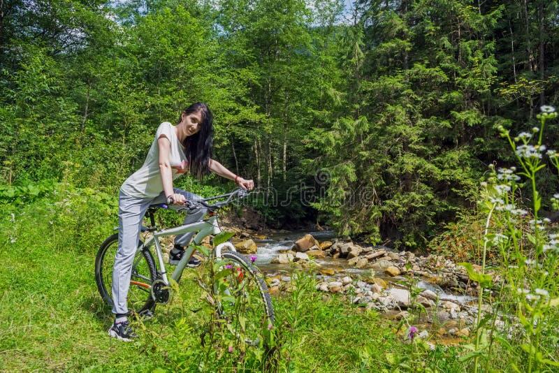 A mulher nova, bonita senta-se em uma bicicleta, contra o contexto de um rio da montanha foto de stock royalty free