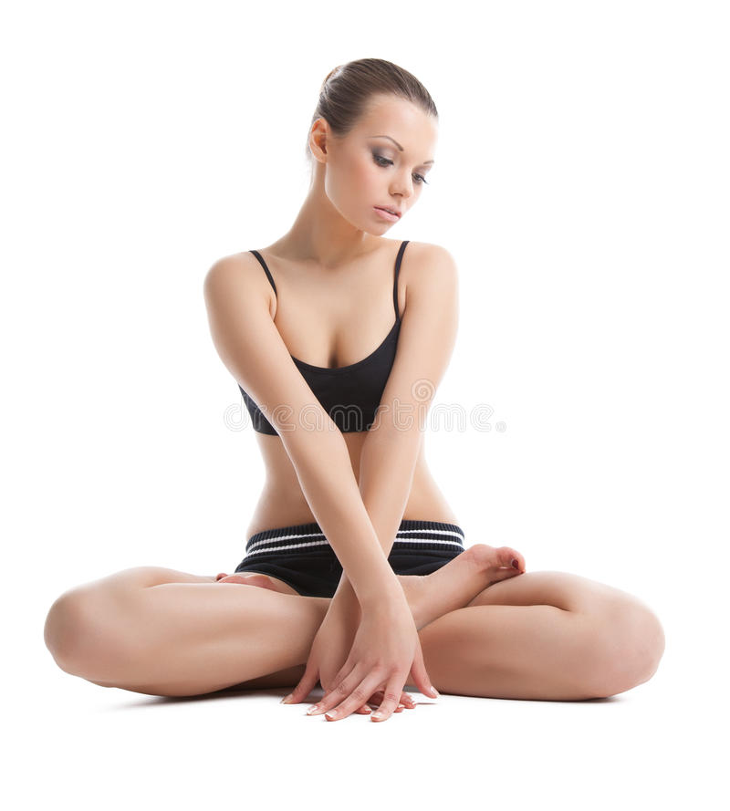 A mulher nova bonita senta-se no pose da ioga dos lotos fotografia de stock