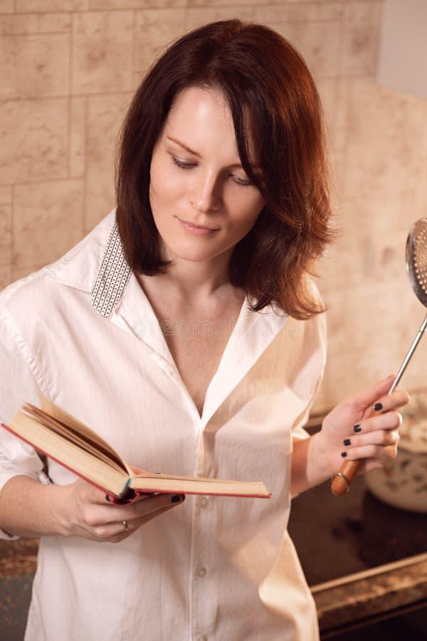 Mulher nova bonito do ruivo que lê um livro ao cozinhar na cozinha fotografia de stock