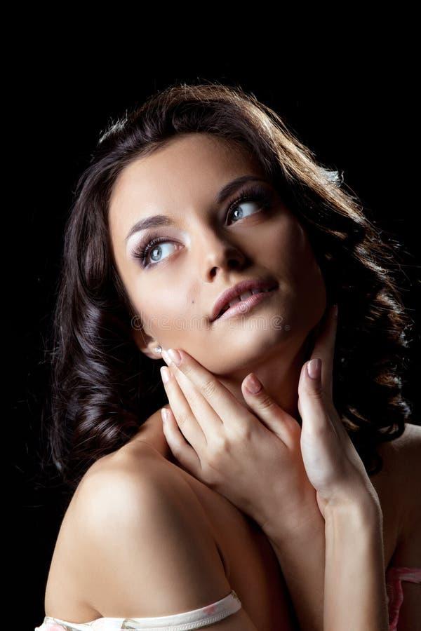 Mulher nova bonito que levanta com mãos na obscuridade fotos de stock royalty free