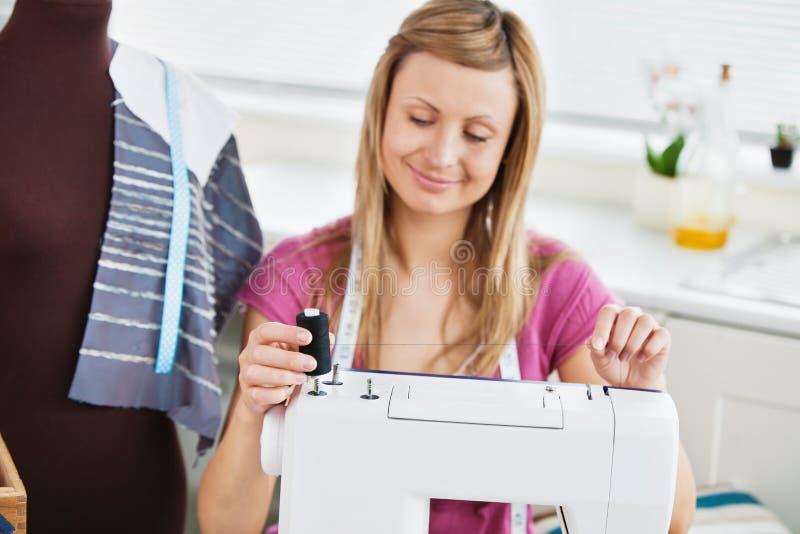 Mulher nova brilhante que usa sua máquina de costura imagem de stock royalty free