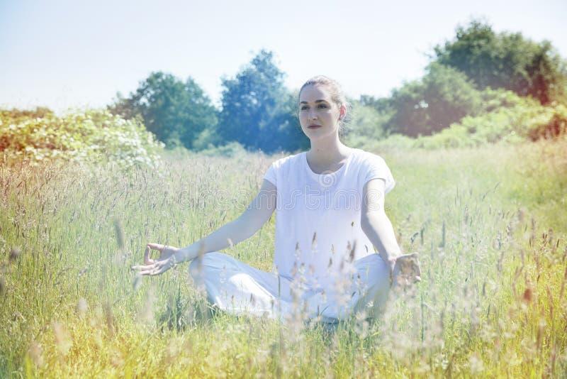 Mulher nova calma da ioga que medita para a paz e a solidão, tonificada imagens de stock