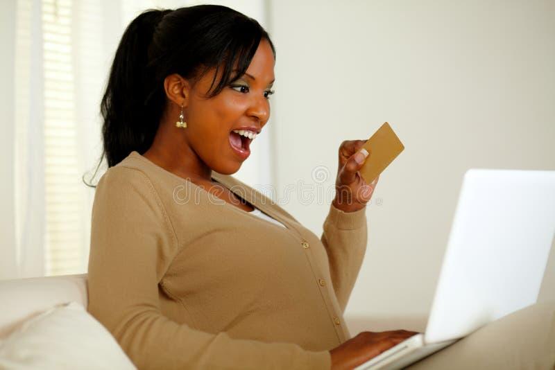 Mulher nova Charming que prende um cartão de crédito do ouro fotos de stock royalty free