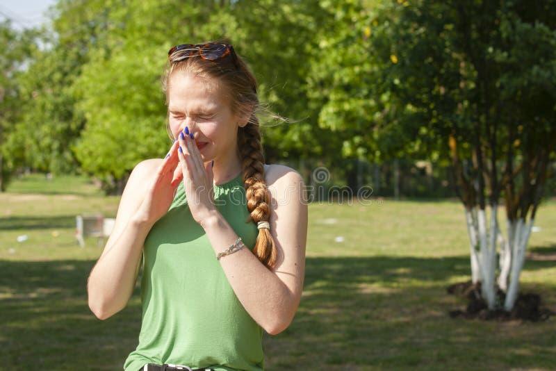 A mulher nova com alergia durante o dia ensolarado est? limpando seu nariz imagens de stock