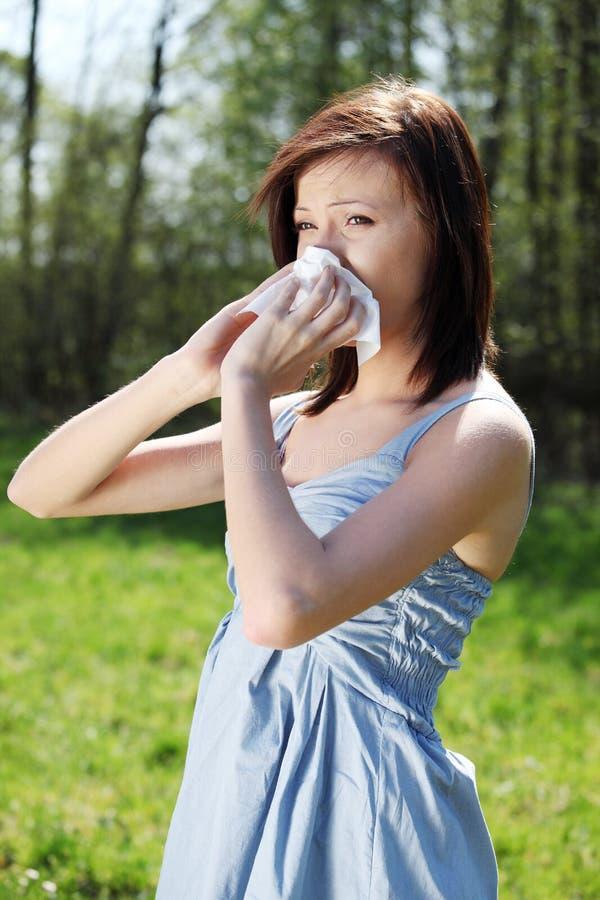 Mulher nova com a alergia que limpa seu nariz runny imagens de stock royalty free
