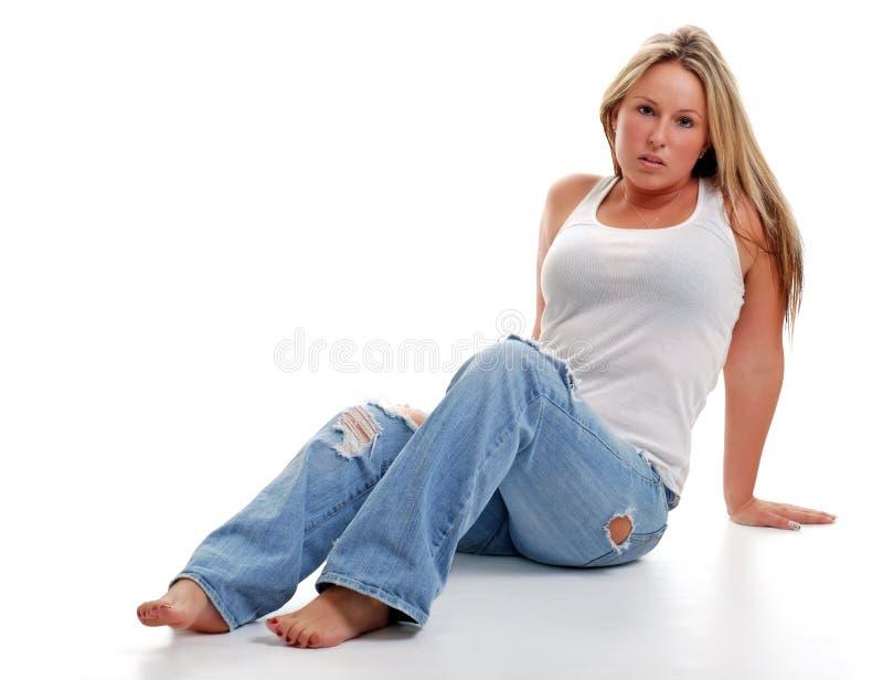 Mulher nova com as calças de brim rasgadas que sentam-se para baixo fotografia de stock royalty free