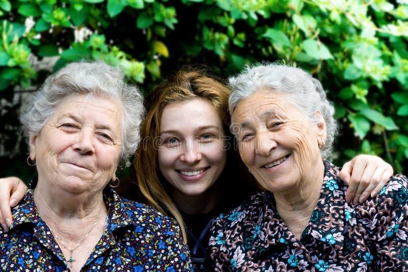 Mulher nova com as duas senhoras sênior imagens de stock