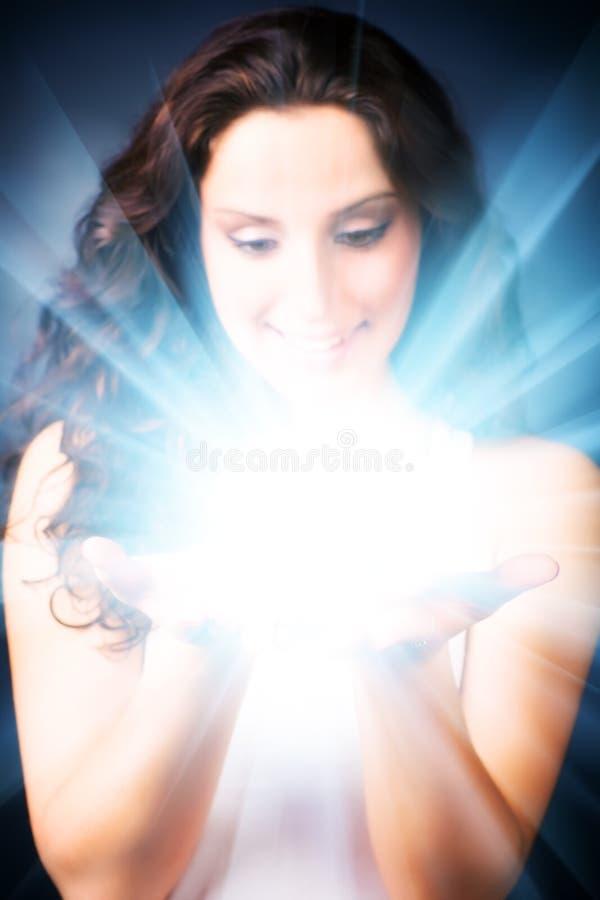 Mulher nova com brilho mágico nas mãos foto de stock