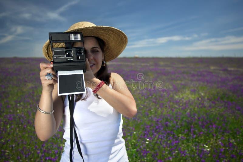 Mulher nova com a câmera imediata da foto fotografia de stock