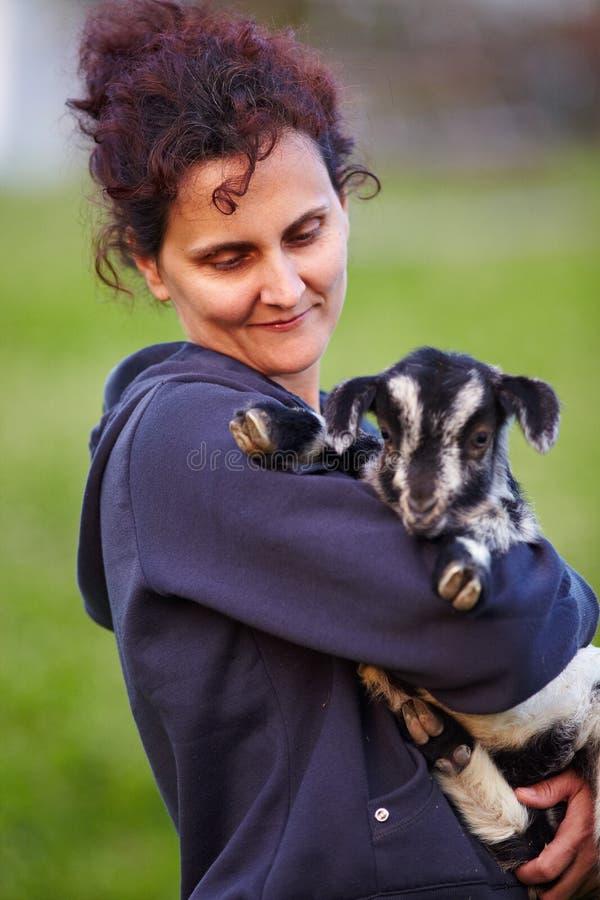 Mulher nova com a cabra do bebê ao ar livre fotografia de stock royalty free
