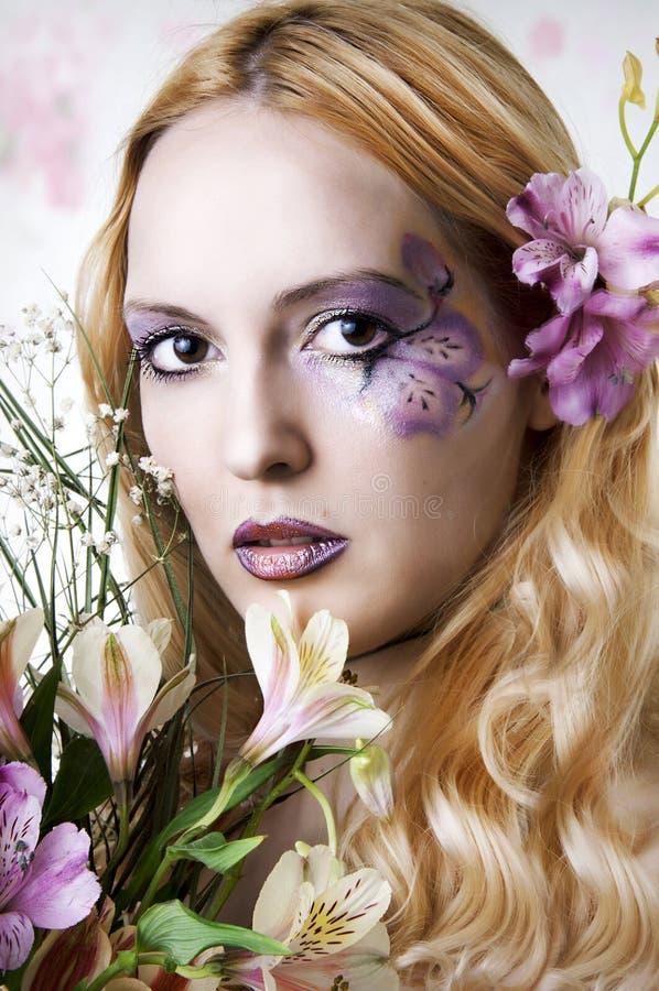 Mulher nova com composição e as flores exóticas imagens de stock royalty free