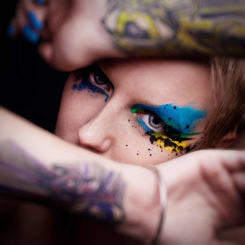 A mulher nova com composição e azul do encanto prega o miliampère fotos de stock royalty free