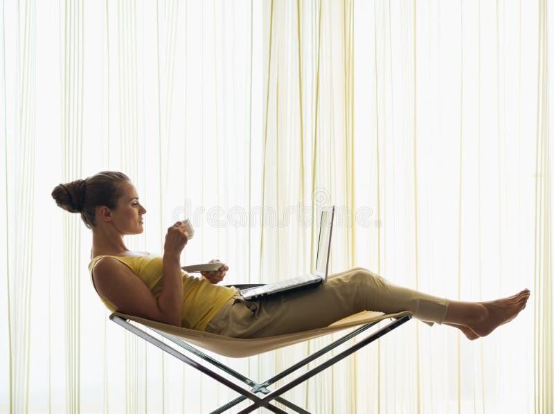 Mulher nova com copo de café usando o portátil em casa foto de stock