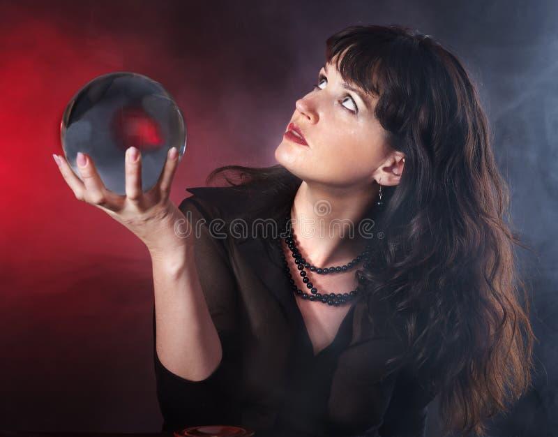 Mulher nova com esfera de cristal. imagem de stock
