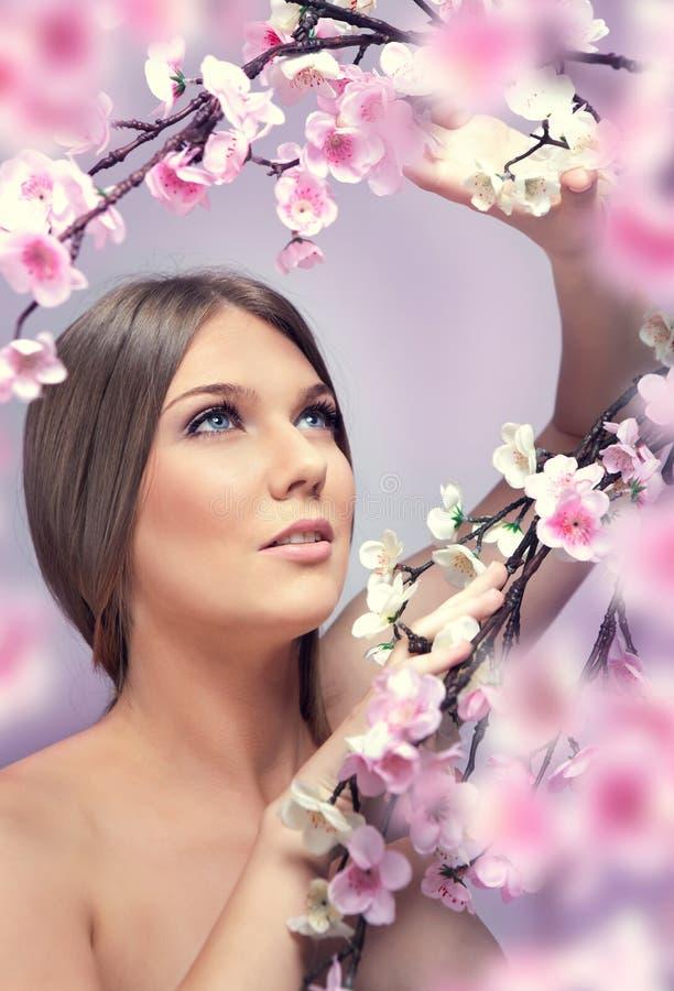 Mulher nova com flores da mola fotografia de stock royalty free
