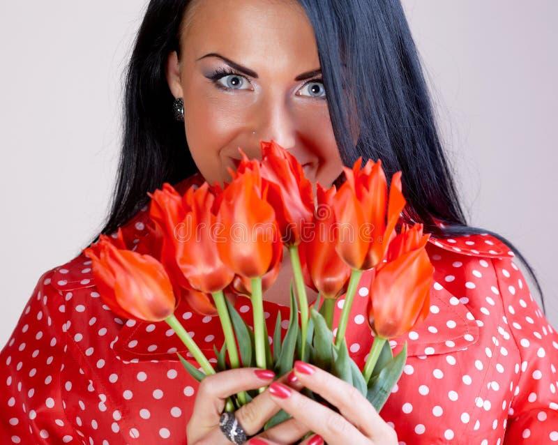 Mulher nova com flores vermelhas foto de stock royalty free