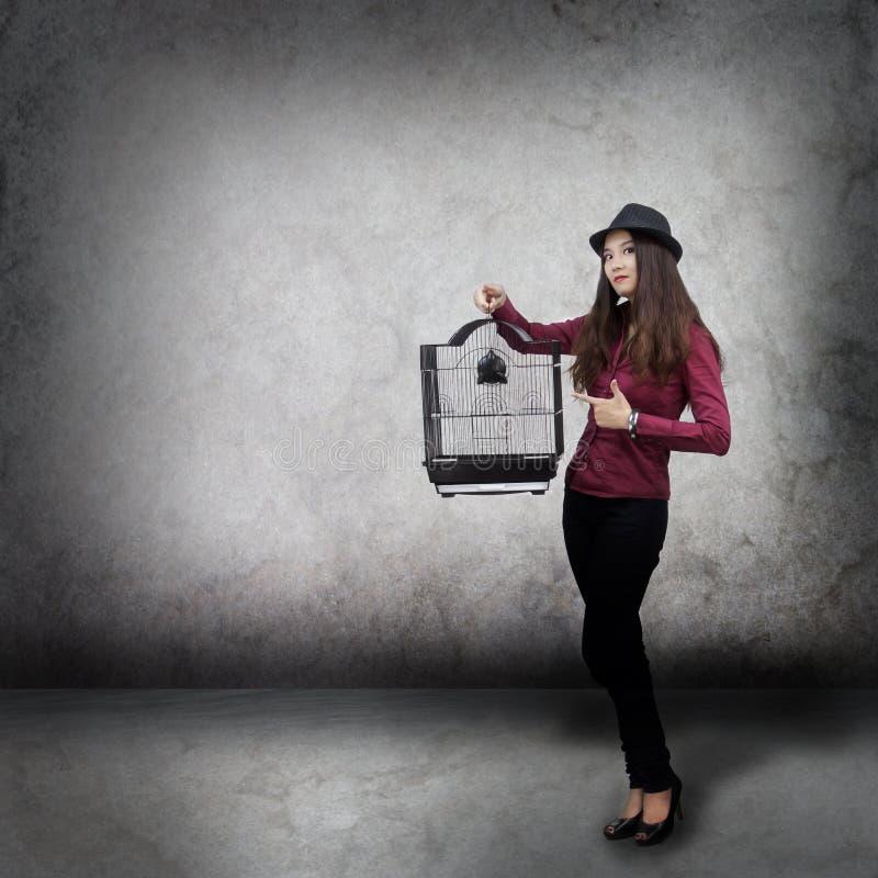 Mulher nova com gaiola de pássaro imagens de stock