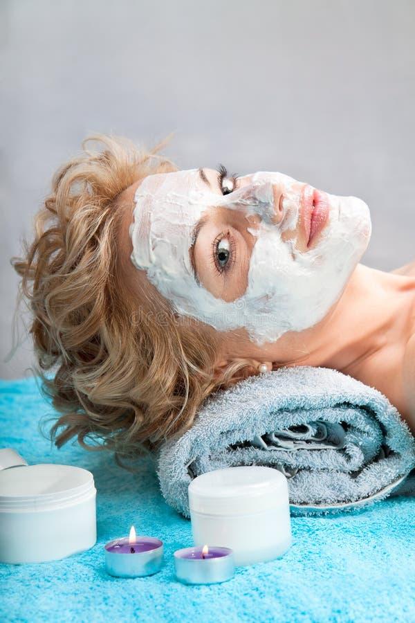 Mulher nova com máscara do facial da argila fotografia de stock