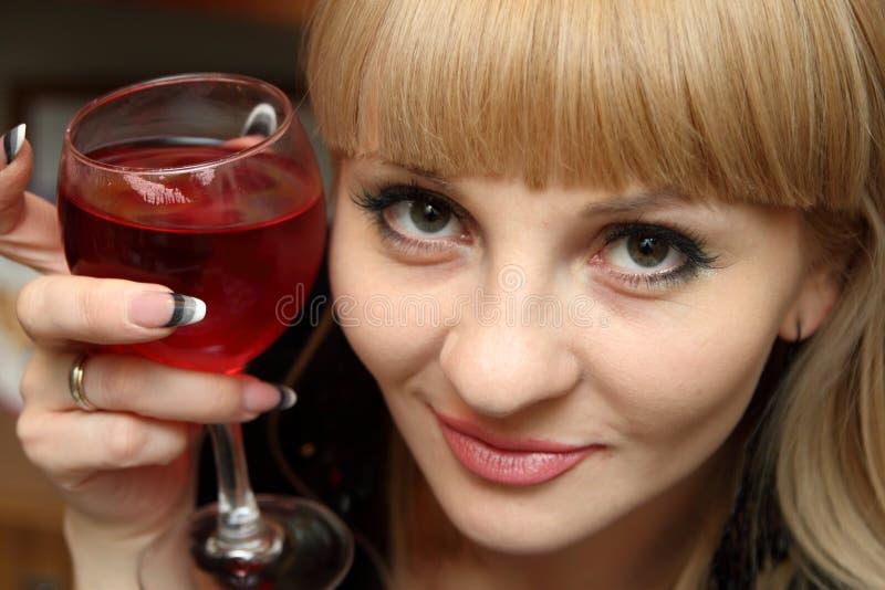 Mulher nova com o bocal do vinho vermelho. fotografia de stock royalty free