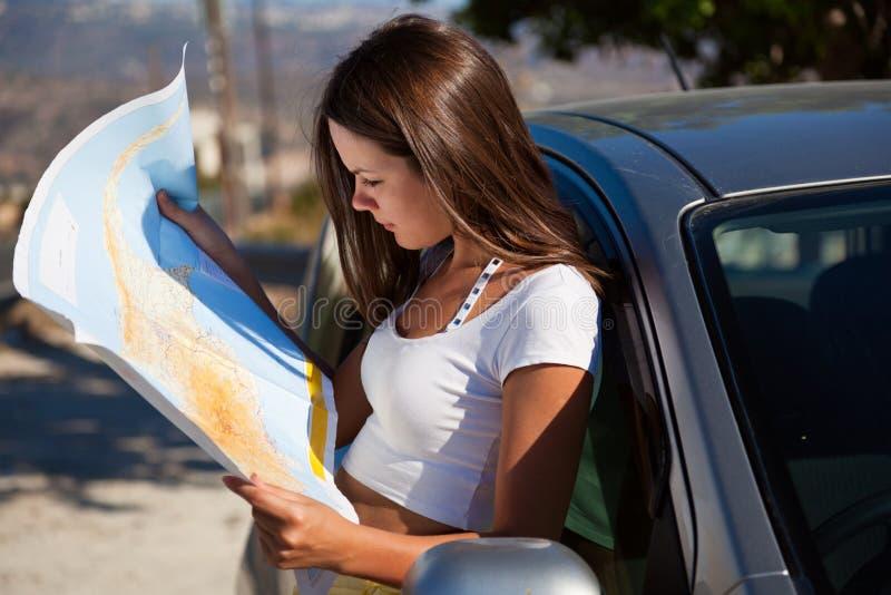 Mulher nova com o mapa perto do carro fotos de stock royalty free