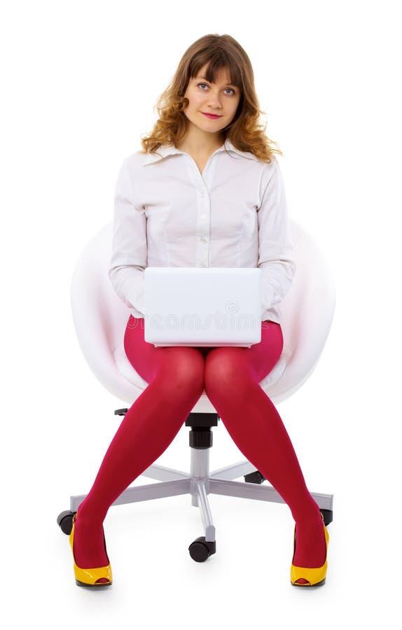 Mulher nova com o portátil pequeno na cadeira imagem de stock