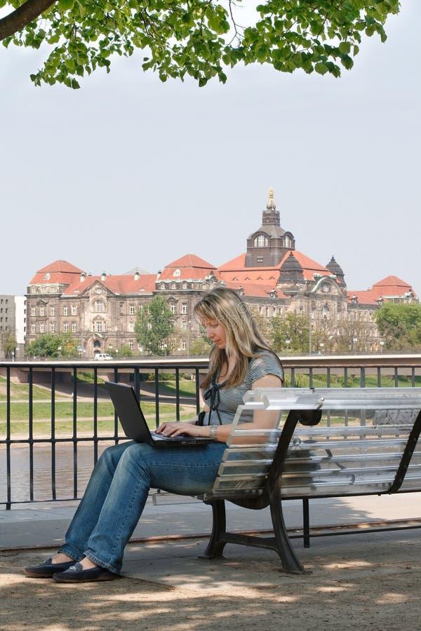 Mulher nova com o portátil que senta-se no banco. foto de stock
